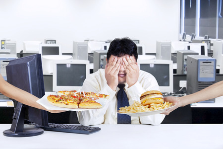 Foto de Overweight businessman try to healthy life and avoid a temptation of fast food - Imagen libre de derechos