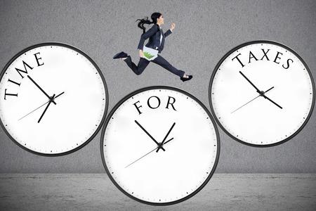 Foto de Concept of time for taxes with a businesswoman running on watch - Imagen libre de derechos