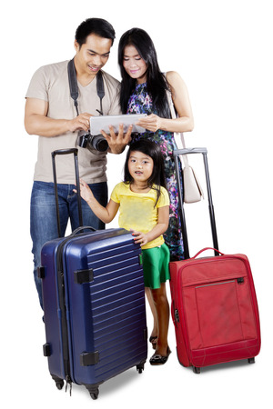 Photo pour Cheerful family carrying luggage to holiday and looking an online map on the digital tablet - image libre de droit
