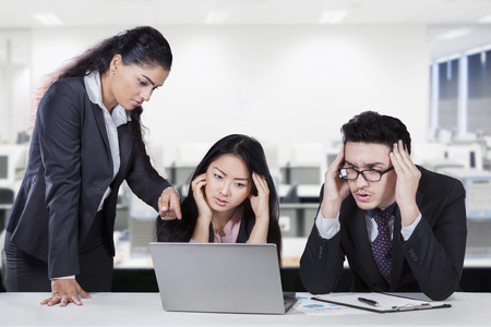 Photo for Young female entrepreneur pointing at the laptop to show the mistake of her subordinates - Royalty Free Image