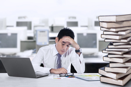 Overworked businessman with laptop and a stack of books in the office