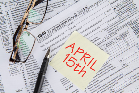 Closeup of the deadline time of tax with the tax form and glasses