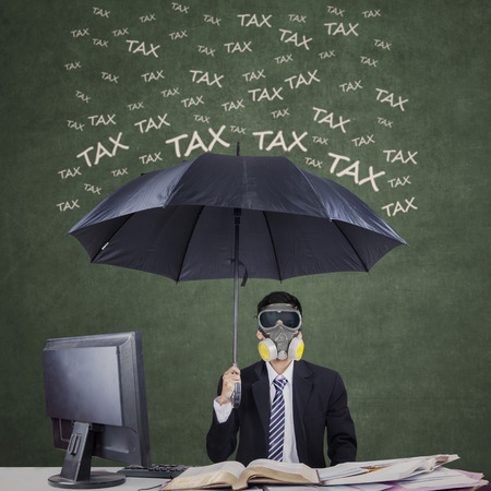 Photo pour Businessman wearing a gas mask and umbrella to protect him from tax - image libre de droit