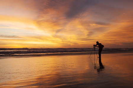 Photo for Male photographer taking picture with dslr camera on the beach at sunset time - Royalty Free Image