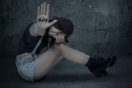 Lonely teenage girl sitting on the floor with a wall background, showing hand with a help text
