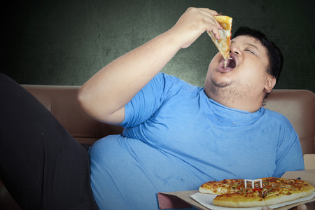 Photo pour Obese person eats pizza while sitting on couch at home - image libre de droit
