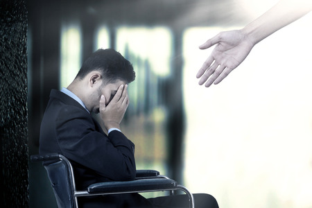 Photo pour Frustrated businessman sitting on a wheelchair,  get a help from a hand - image libre de droit