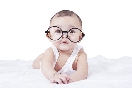 Foto de Portrait of little baby boy looking at the camera while lying on bed and wearing a round glasses - Imagen libre de derechos