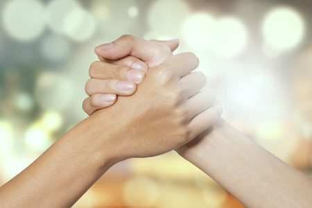 Foto de Closeup of two hands joining together, symbolizing to trust each other, shot with a bokeh background - Imagen libre de derechos