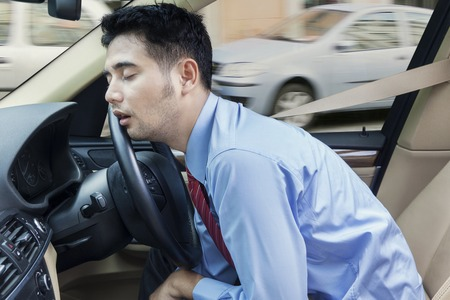 Photo pour Male entrepreneur sleeping in the car while driving on the road at traffic jam - image libre de droit
