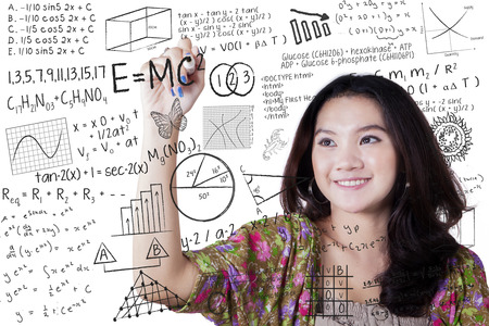 Photo pour Smart female high school student writing various high school math and science formula - image libre de droit