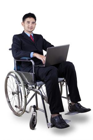 Foto de Young disabled businessman wearing formal suit and sitting on wheelchair while holding a laptop computer - Imagen libre de derechos