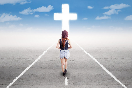 Photo pour Rear view of young girl doing a spiritual journey by following a cross on the road - image libre de droit