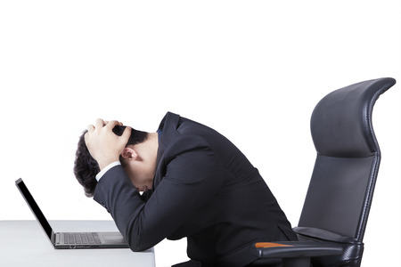 Photo pour Portrait of stressful male worker sitting on office chair while holding his head with a laptop on desk, isolated on white - image libre de droit