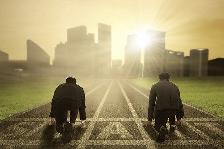 Foto de Rear view of two worker wearing formal suit and kneeling on the start line to compete - Imagen libre de derechos