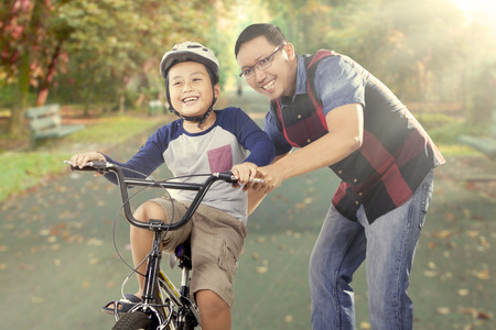 Foto de Cute little boy try to ride a bike with his father on the road at the park, shot outdoors - Imagen libre de derechos