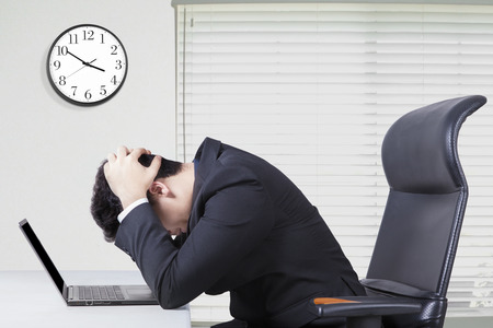 Photo for Young entrepreneur sitting in the office and looks confused with a laptop on desk and clock on the wall - Royalty Free Image