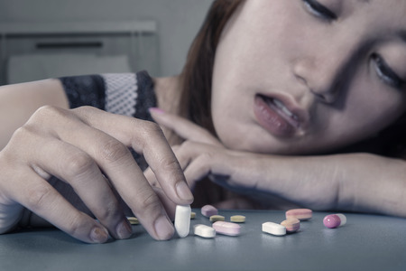 Foto de Depressed female drug addict holding pills on the table, shot at home - Imagen libre de derechos