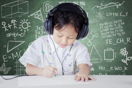 Foto de Female kindergarten school student studying in the classroom while wearing headphones and write on the paper - Imagen libre de derechos