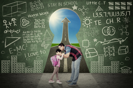 Photo pour Young father kiss his daughter before going to school in front of a key hole with scribble and upward arrow - image libre de droit