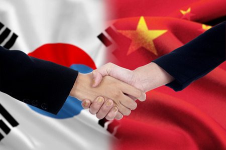 Photo pour Two politicians shaking hands after good deal in front of the chinese and south korean flags - image libre de droit