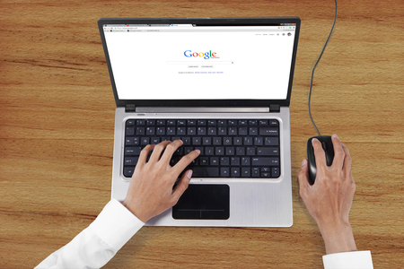 Photo pour JAKARTA, SEPTEMBER 08, 2015: Image of worker hands using laptop to open google search web page - image libre de droit
