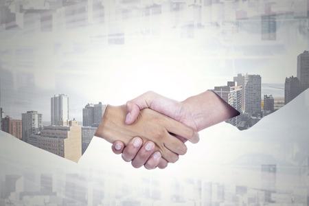 Foto de Double exposure of two businesspeople shaking hands with office building background - Imagen libre de derechos