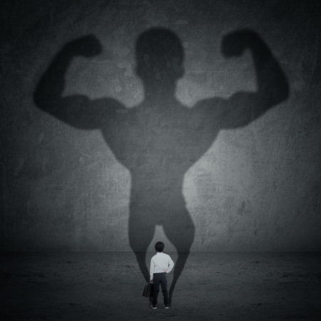 Foto per Little businessman casting a shadow of an athlete - business and career strength concept - Immagine Royalty Free