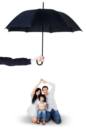 Foto de Portrait of joyful parents and their daughter sitting in the studio under umbrella. Life and family insurance concept - Imagen libre de derechos