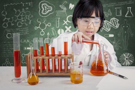 Foto de Portrait of little chemist doing experiment for healthcare with chemical fluid in the laboratory - Imagen libre de derechos