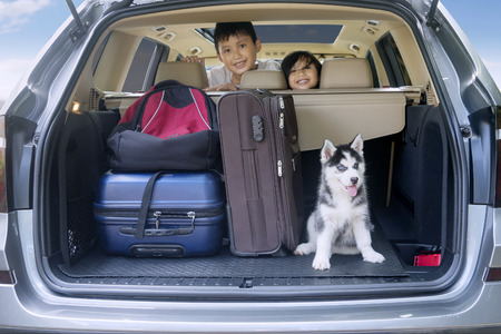 Photo pour Two cheerful children smiling inside a car with husky dog and luggage for traveling - image libre de droit