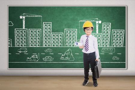 Foto de Picture of a little architect carrying blueprint and briefcase with a picture of buildings on the blackboard - Imagen libre de derechos