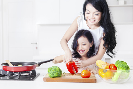 Photo for Portrait of happy mother and her daughter cooking together in the kitchen while cutting vegetable - Royalty Free Image