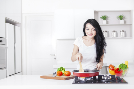 Foto de Portrait of a beautiful woman cooking vegetable on the stove with frying, shot in the kitchen at home - Imagen libre de derechos