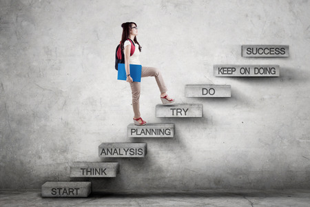 Photo for Image of a female high school student walking on the stairs while carrying backpack with strategy plan leading to success - Royalty Free Image