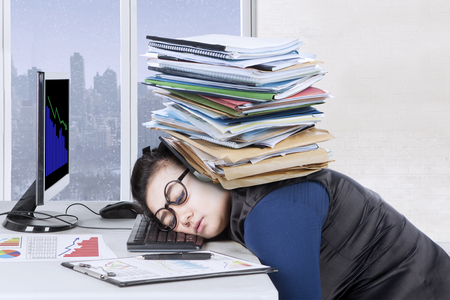 Photo pour Female entrepreneur feels tired with pile of documents over head while sleeps on the desk, winter background on the window - image libre de droit