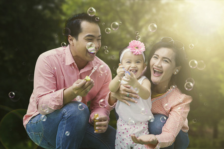 Foto de Portrait of cheerful family playing with soap bubbles while laughing together in the park - Imagen libre de derechos