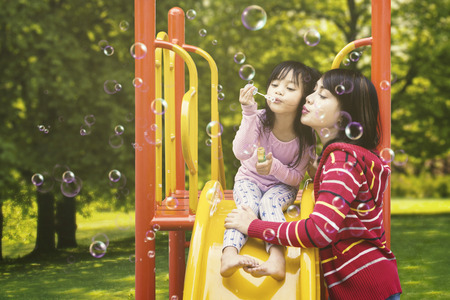 Photo pour Photo of a beautiful mother and her daughter blowing soap bubbles on the playground at the park - image libre de droit