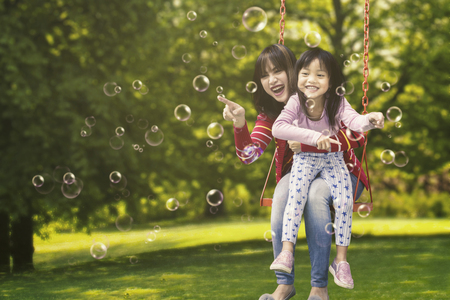Photo for Cheerful little girl and her mother sitting on a swing while touching soap bubbles - Royalty Free Image