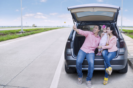 Photo pour Happy family sitting behind the car while taking selfie picture by using smartphone at the street - image libre de droit