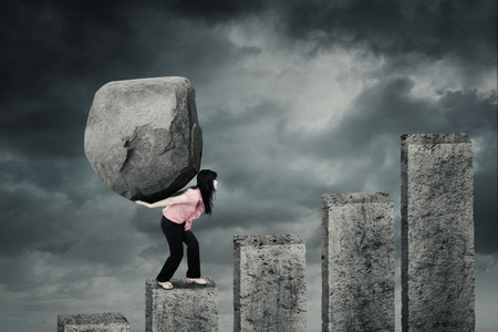 Photo pour Female entrepreneur climbing a financial chart while carrying a big stone on her back with cloudy sky - image libre de droit