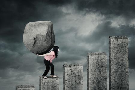 Foto de Female entrepreneur climbing a financial chart while carrying a big stone on her back with cloudy sky - Imagen libre de derechos