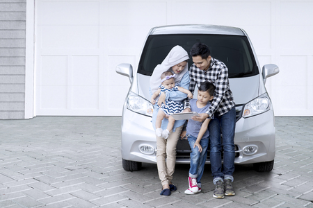 Photo pour Picture of Muslim family sitting in front of a car while using a digital tablet in the house garage - image libre de droit