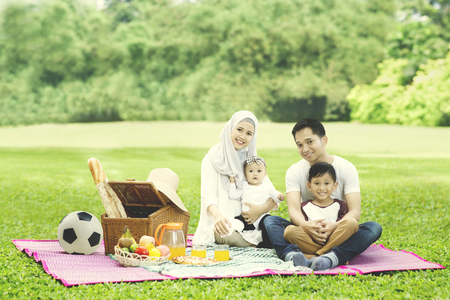 Photo pour Image of Muslim family smiling at the camera while picnicking in the park - image libre de droit