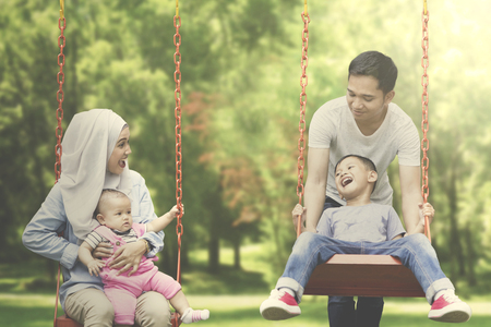 Image of Muslim parents spending time with their children while playing swing in the park