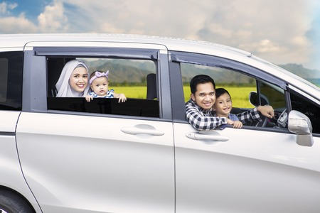 Photo pour Portrait of Muslim family looking out of a car window while driving for travel on vacation - image libre de droit