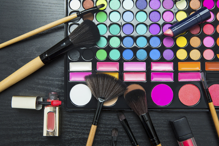 Close up of make up brushes and cosmetics with palette eyeshadow on dark background