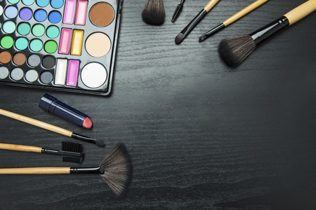 Make up brushes and eyeshadow palette on wooden background with copy space