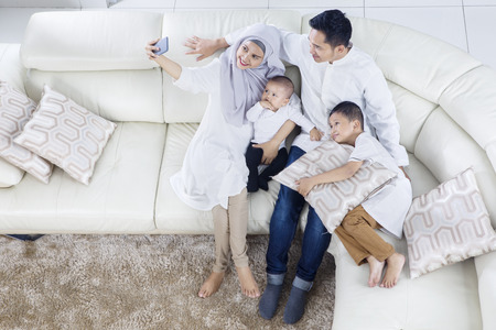 Foto de Top view of muslim family taking selfie photo while smiling and sitting on the sofa together - Imagen libre de derechos