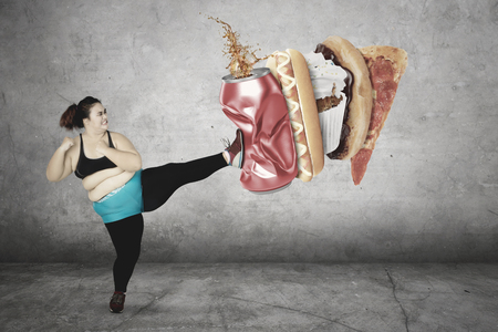 Photo for Diet Concept. Overweight woman kicks a can of soft drink and junk foods while wearing sportswear. Isolated on white background - Royalty Free Image